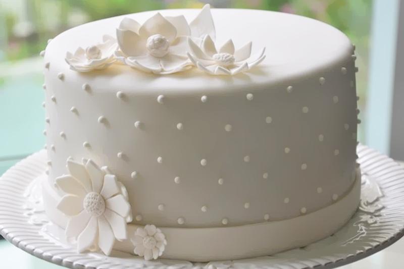 Flores e decoração com a mesma cor do bolo deixa-o mais discreto