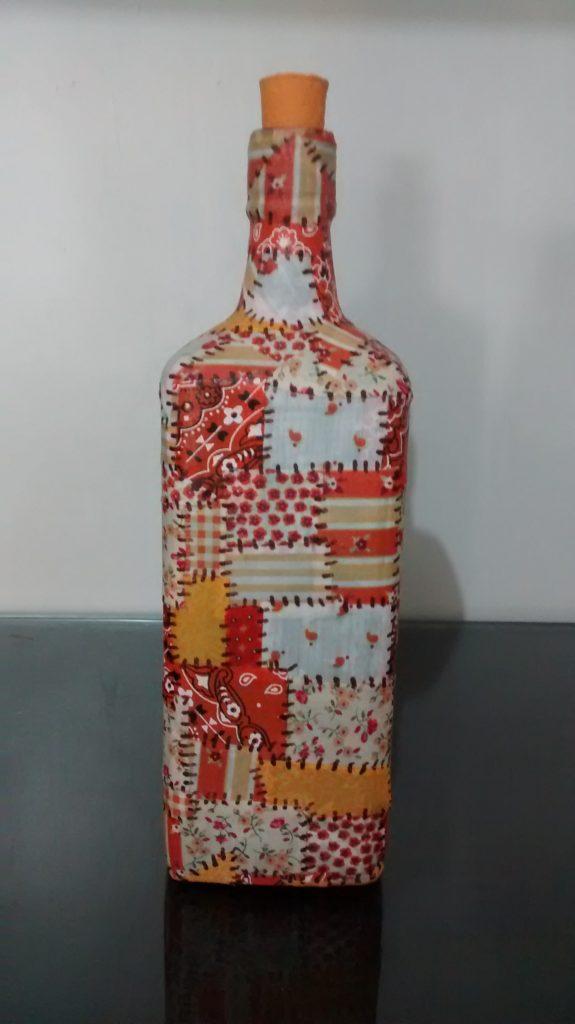 Você pode usar retalhos de tecidos para enfeitar sua garrafas, o resultado final é incrível