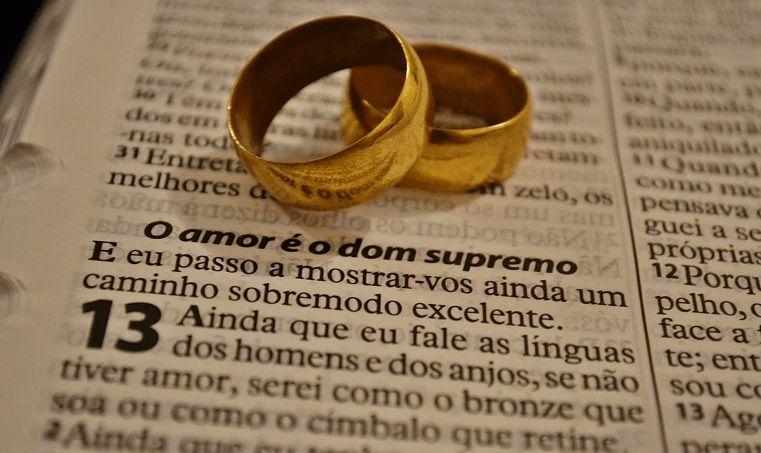 aliança de casamento em cima da bíblia, perto de um versículo sobre amor
